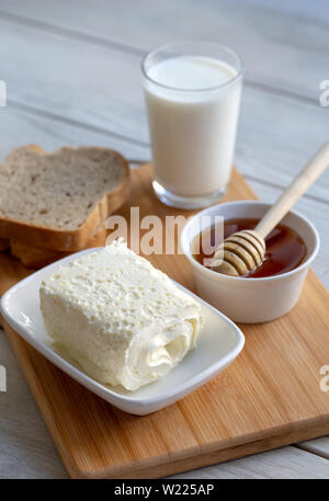 Clotted cream (butter cream) for Turkish breakfast / Kaymak, honey and glass of milk - Stock Photo