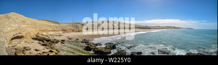 Scenic panorama of sand dunes and the Atlantic ocean with cloudy blue clear sky on Ad Dakhla peninsula in South of Morocco - Stock Photo