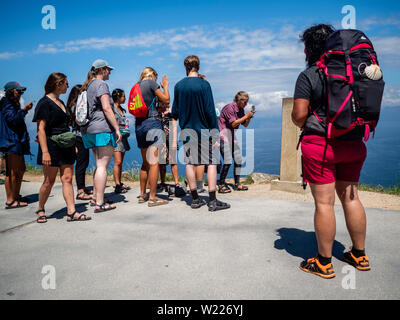 June 27, 2019 - Finisterra, A Coruña, Spain - A group of pilgrims are seen taking photos at the km 0 marker. Cape Finisterre is the destination of those pilgrims who, after visiting the St James' tomb is Santiago, continue their way along the route marked out for them overhead by the Milky Way until they could go no further. Finisterre was considered during the period of Classical Antiquity to be the end of the known world. Finisterre, or Fisterra in Gallego, the local Galician dialect, means ''Land's End'' in Latin. Next, to the lighthouse,  there is the 0.0 Kilometer Marker from where the - Stock Photo
