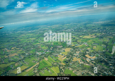 the view of green field and farm and city downtown in middle of Thailand. It shot from Jetplane. - Stock Photo