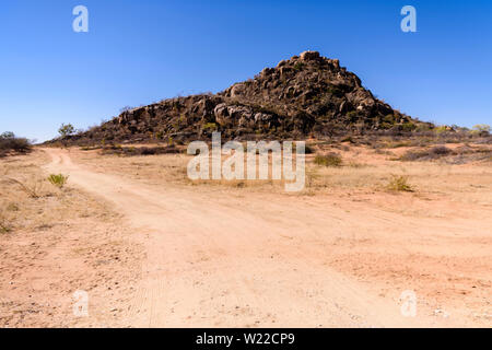 Gravel dirt road beside a boulder mound created by glacial erosion in Central Namibia - Stock Photo