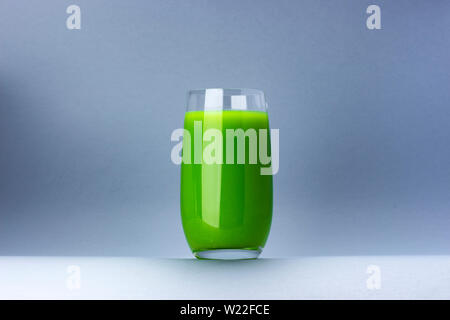 Glass of green juice isolated on white background with copy space for text, fresh apple and celery cocktail - Stock Photo