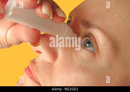 Middle aged woman drops eyes. Macro closeup image of face. Medical procedure at home. Girl holds eyedropper bottle and dropping - Stock Photo