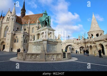 Tourists explore the southern courtyard of the Fisherman's Bastion alongside St Matthias Church, two of the top attractions of Budapest. - Stock Photo