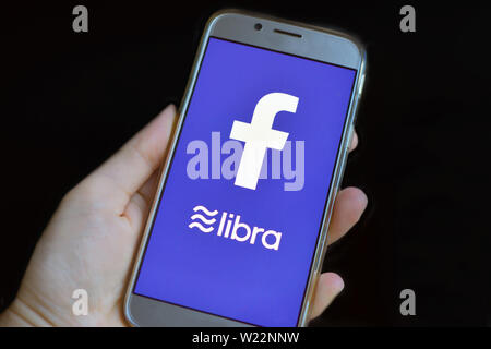 Cryptocurrency Libra concept with hand holding cellphone with Libra and Facebook logo on bue mobile phone - Stock Photo