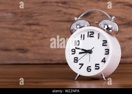 white alarm clock on wooden old background, red vintage clock on wooden table - Stock Photo