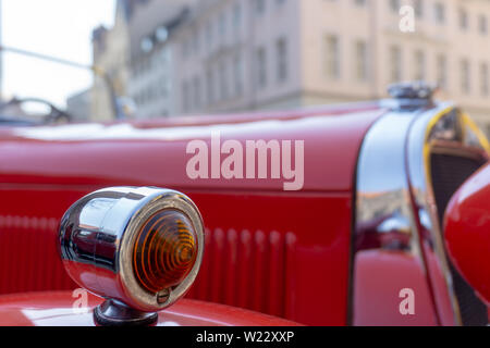 Sharply focused indicator of a red vintage car, deliberately blurred in the background, Bokeh - Stock Photo