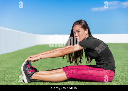 Fitness woman stretching hamstring leg muscles - back stretch sitting toe touch stretches. Seated forward bend. Sporty young athlete in activewear exercising flexibility on grass in sunny outdoor gym. - Stock Photo