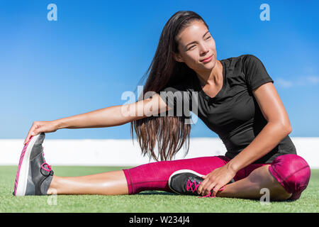 Fitness woman stretching one leg toe-touch stretch exercising hamstring and glute muscles stretches. Sporty Asian athlete exercising sitting forward bend legs exercise on grass in sunny outdoor gym. - Stock Photo