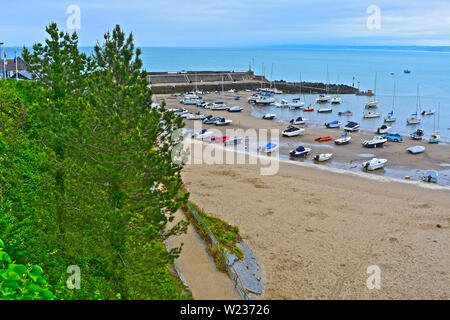 A view of the pretty little harbour at Newquay in West Wales, at low tide. Sandy beach and stone breakwater. Assorted leisure craft & fishing boats. - Stock Photo