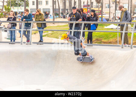 LOS ANGELES, CALIFORNIA, USA - May 11, 2019: Concrete ramps and palm trees at the popular Venice beach skateboard park in Los Angeles, California - Stock Photo