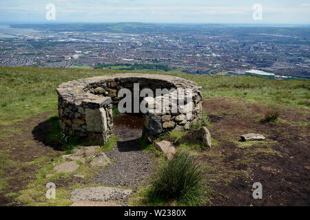 Belfast City from Dry Stone Shelter on the Black Mountain Ridge Trail in County Antrim, Northern Ireland, UK. - Stock Photo