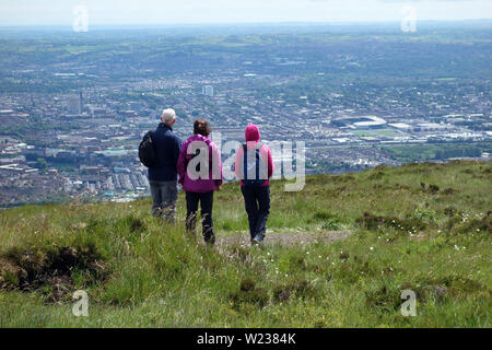 Three Walkers Looking down on Belfast City from the Black Mountain Ridge Trail in County Antrim, Northern Ireland, UK. - Stock Photo