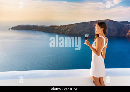 Luxury hotel terrace. Europe destination summer vacation. Asian woman drinking red wine relaxing enjoying view of the mediterranean sea in Oia, Santorini, Greece. Honeymoon high end travel holiday. - Stock Photo