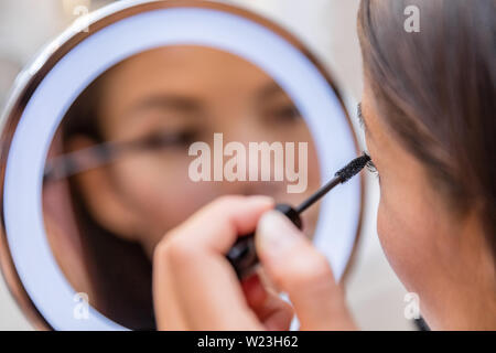 Woman putting mascara in lighted round makeup mirror from luxury hotel or home bathroom. Beautiful Asian girl getting ready for a night out applying eye make-up with brush looking at reflection. - Stock Photo
