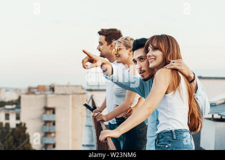 Group of friends enjoying outdoors at roof. Young friends at sunset on penthouse patio