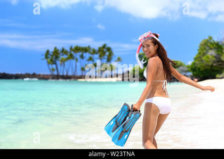 Happy beach vacation girl having fun doing snorkel watersport activity in caribbean ocean. Asian woman enjoying swimming in tropical destination vacation travel holidays on white sand beach. - Stock Photo