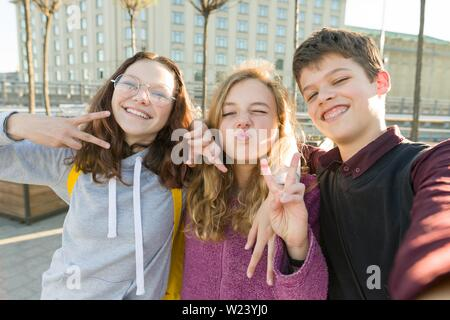 Portrait of friends teen boy and two girls smiling, making funny faces, showing victory sign in the street. City background, golden hour - Stock Photo