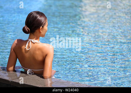 Luxury travel wellness resort bikini woman relaxing in swimming pool. Hydrotherapy spa retreat from behind on side of infinity pool looking away at blue water copyspace. Relaxation vacation concept. - Stock Photo