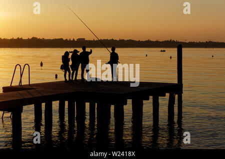 Group of young people fishing and talking on pier, unrecognizable persons - Stock Photo