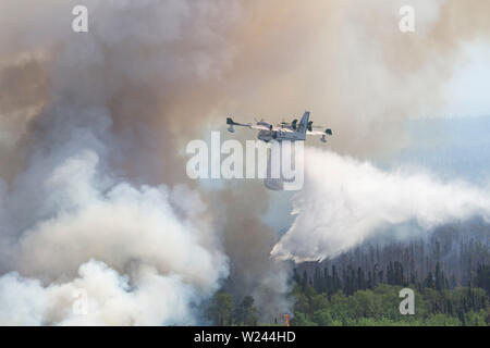 Talkeetna, Alaska. 04th July, 2019. A Bombardier 415 Superscooper aerial firefighting aircraft drops water on a wildfire burning near Montana Creek July 4, 2019 near Talkeetna, Alaska. Credit: Planetpix/Alamy Live News - Stock Photo