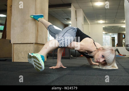 Young blonde female gymnast doing handstand in gym, copyspace - Stock Photo
