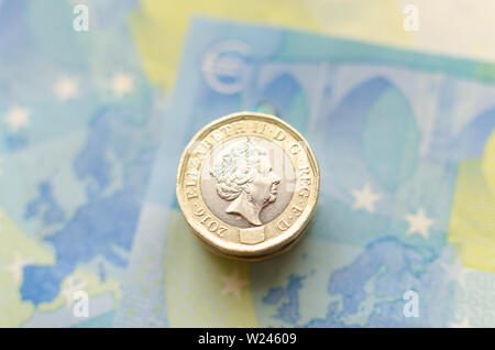 Close up photo of one Pound coins on top of 20 Euro banknotes. - Stock Photo