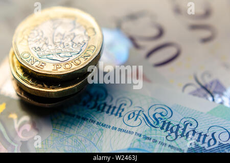 Macro photo of British one Pound coins on top of the banknotes of different denomination. - Stock Photo