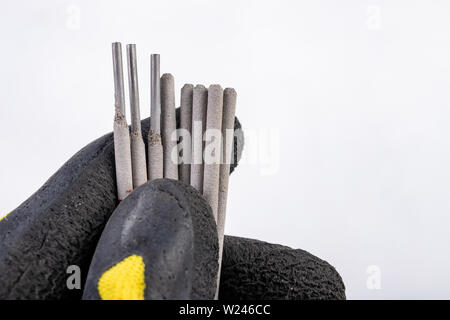 Electrodes for electric welding held in the palm of your hand. Welding accessories for MMA methods. Light background. - Stock Photo