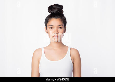 serious confident asian woman in white Top staring at camera