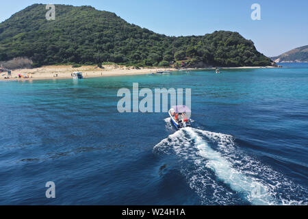 Small boat with tourists heading to iconic small uninhabited island of Marathonisi featuring clear water sandy shore and natural hatchery of Caretta-C - Stock Photo