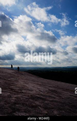 Two hikers climb Enchanted Rock - Stock Photo