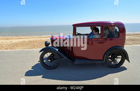 Classic Red Austin Seven Car being driven along Seafront  Promenade. - Stock Photo