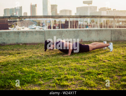 Young athletic man doing pushups exercises at park - Stock Photo