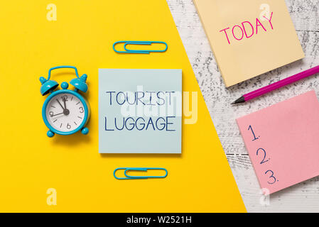Handwriting text writing Tourist Luggage. Conceptual photo big bag that contains everything one needs for traveling Notepads clips colored paper sheet - Stock Photo