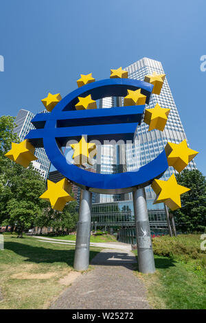 Frankfurt, Germany. July 2019.  The Symbol of Euro monument in front of the Eurotower - Stock Photo