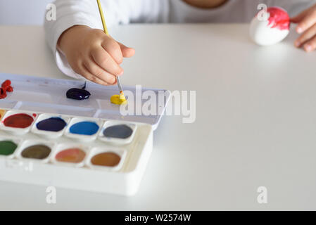 Child hands painted Easter eggs, paints and brushes on white table. Preparation for the Easter. Kid hands draw with colors. - Stock Photo