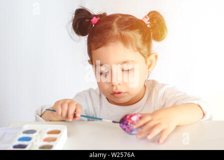Happy easter. Funny little girl painting Easter eggs. Happy toddler preparing for Easter. - Stock Photo
