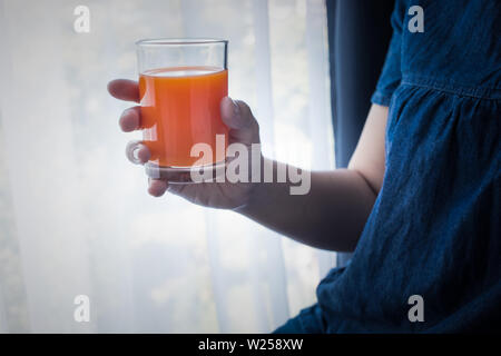 Female hand holding cup of orange juice in morning when she wake up.healthy  lifestyle concept ideas - Stock Photo