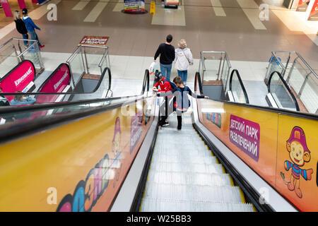 Chelyabinsk region, Russia - June 2019. Buyers go down the escalator at TRNK Rodnik - Stock Photo