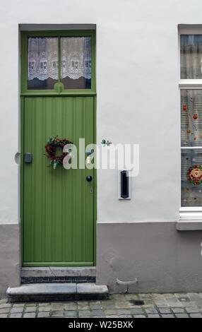 Vintage green front door decorated with Christmas wreath shot in Bruges, Belgium. Old green door with window at the top. - Stock Photo