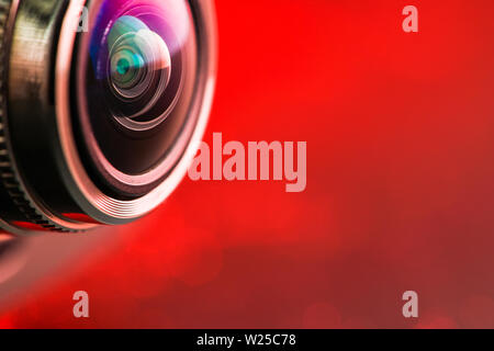 Camera lens with red backlight. Side view of the lens of camera on red background. Camera Lens close Up. Optics - Stock Photo
