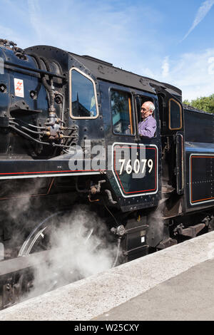 A close up of the driver on steam train 76079.  The train prepares to depart Grosmont Station, on the North Yorkshire Moors Railway. - Stock Photo