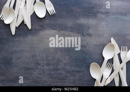 Top view of scattered wooden cutlery - spoons, forks and knifes on marble black kitchen counter. Copy space for text. - Stock Photo