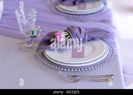 Magnificent table appointments of a classical wedding in lilac color - Stock Photo