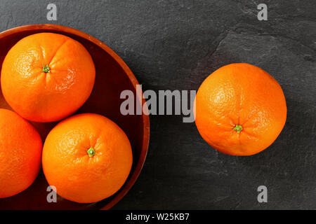 Top down view, whole oranges in wooden bowl, one next to it on black stone board. - Stock Photo