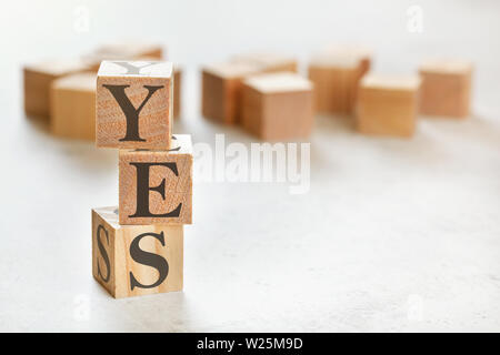 Three wooden cubes with letters AAA means CCC , on white table, more in background, space for text in right down corner - Stock Photo