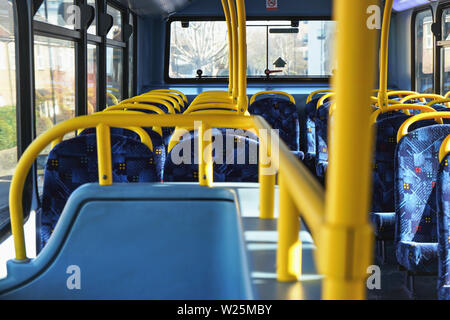 Sun shines on empty interior of London double decker bus, yellow holding rails and blue seats - Stock Photo