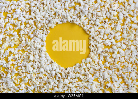 Border of popcorn scattered over yellow background with copy space, top view. Minimalistic design for movie poster, entertainment concept. Close-Up Of - Stock Photo