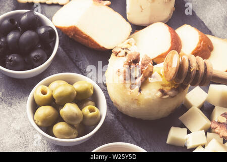 Snacks with wine - various types of cheeses, figs, nuts on a gray background. Toned - Stock Photo